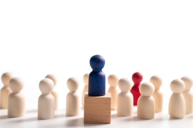 Figura de madeira em pé na caixa para mostrar influência e empoderamento. conceito de liderança empresarial para equipe líder