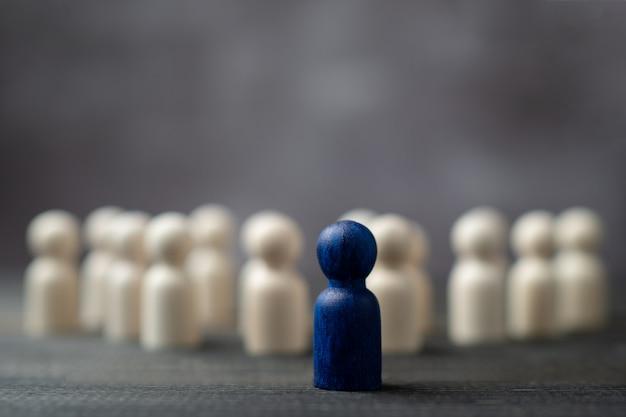 Figura de madeira em pé na frente da equipe para mostrar influência e empoderamento.
