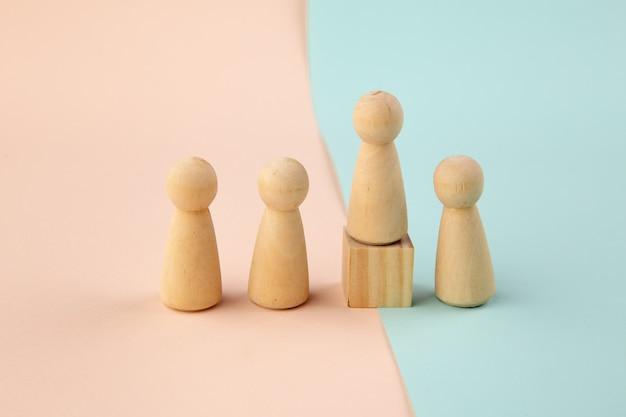 Figura de madeira em pé sobre a caixa para mostrar influência e empoderamento em fundo colorido. conceito de liderança empresarial para a equipe líder.