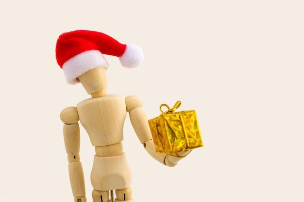 Figura de madeira - manequim de arte com chapéu de papai noel vermelho com caixa de presente. conceito de negócios e design para o natal. foco seletivo