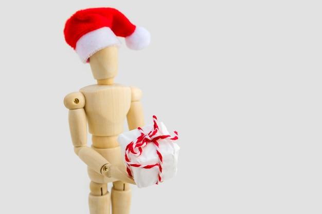 Figura de madeira - manequim de arte com chapéu de papai noel vermelho com caixa de presente. negócios e conceito de design para o natal