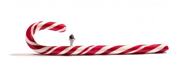 Figura de menino gordo em miniatura em um bastão de doces listrado