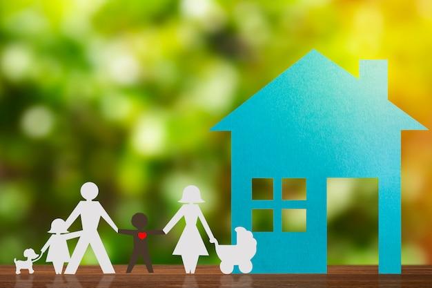 Figura de papel de um casal de mãos dadas com crianças e um filho adotivo preto. casa azul e fundo desfocado. diversidade, conceito de minorias.