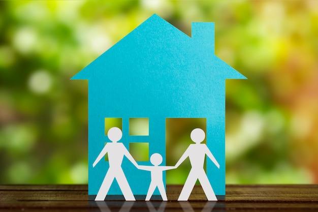 Figura de papel de um casal gay de mãos dadas com o filho adotivo. casa azul e fundo desfocado. diversidade, conceito de minorias.