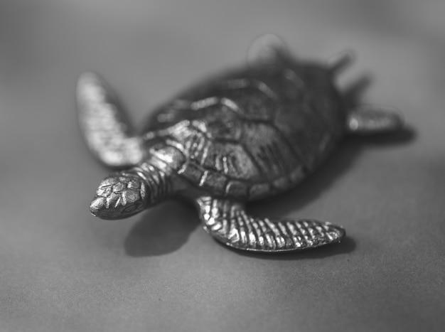 Figura de tartaruga metálica e escura