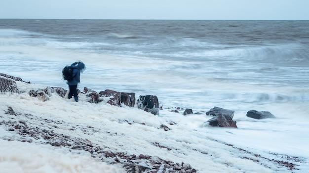 Figura de um homem com uma mochila em um borrão em um vento forte em uma tempestade. costa do mar branco. paisagem dramática do norte