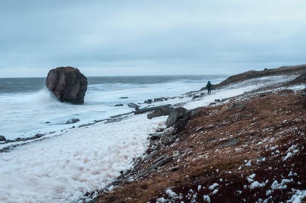 Figura de um homem com uma mochila em um borrão em um vento forte em uma tempestade. costa do mar branco. paisagem dramática do norte.