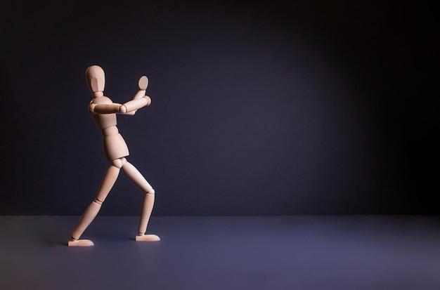 Figura de um homem em um fundo preto gestalt na pose homem de madeira em um fundo preto