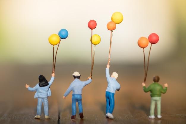 Figura diminuta das crianças com os balões coloridos que estão, andando e jogando junto na tabela de madeira.