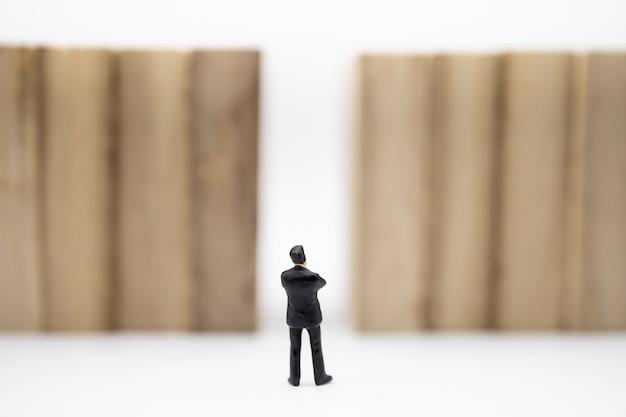 Figura diminuta do homem de negócios que está na frente da parede de madeira do bloco no branco.