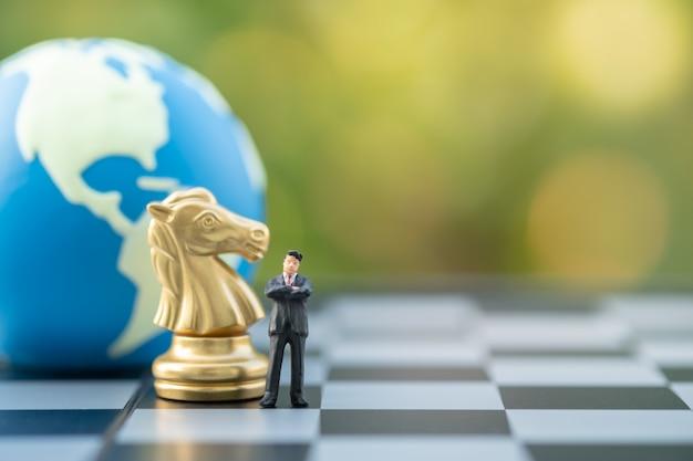 Figura diminuta do homem de negócios que está no tabuleiro de xadrez com xadrez do cavaleiro do ouro e esfera do mundo.