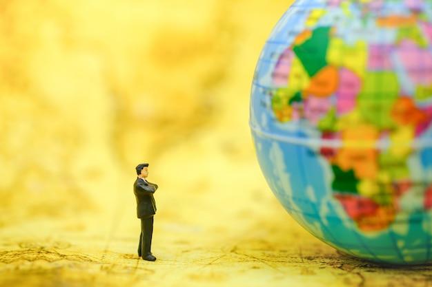 Figura diminuta dos povos do homem de negócios que está no mapa e que olha à mini bola do mundo no mapa.