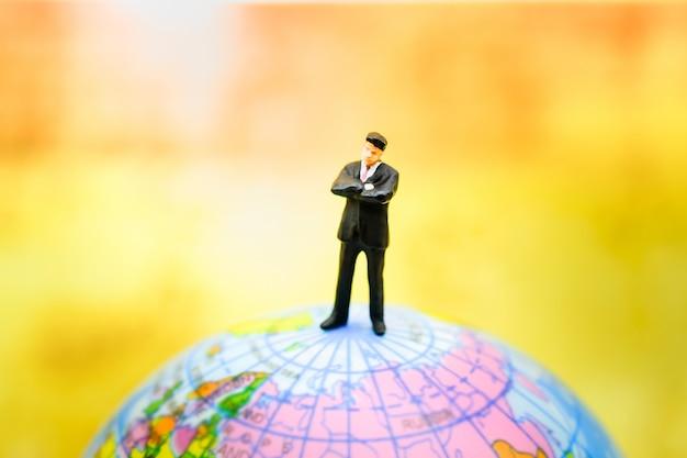 Figura diminuta dos povos do homem de negócios que está no mini modelo da bola do mundo.