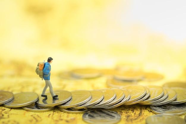 Figura diminuta dos povos do viajante com trouxa que anda em moedas no mapa do mundo.