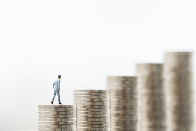 Figura do homem de negócios pequeno que está na primeira etapa de pilhas da moeda com fundos brancos.