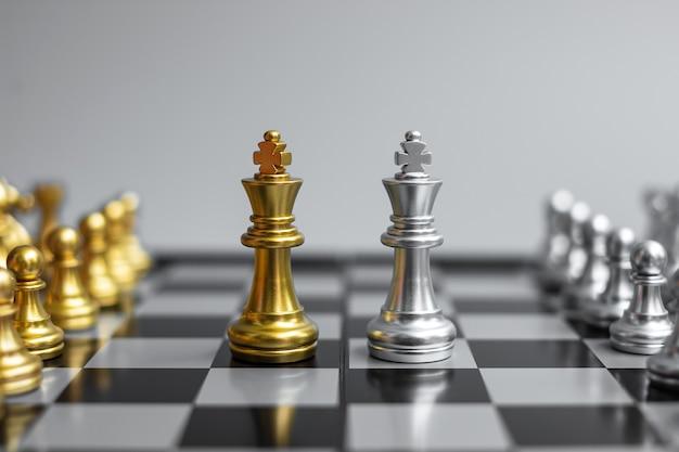 Figura do rei do xadrez de ouro e energia ou oponente do xeque-mate durante a competição do tabuleiro de xadrez.