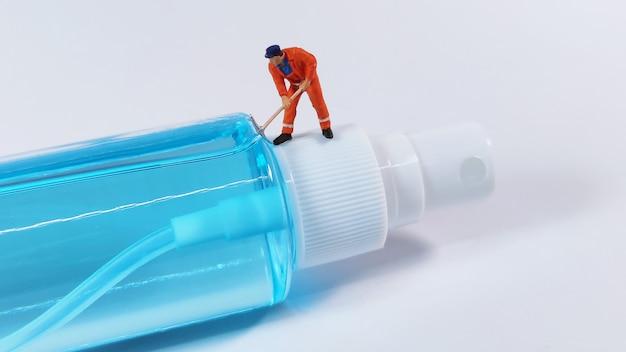 Figura do trabalhador técnico de pé sobre um frasco de spray de álcool. conceito covid-19.