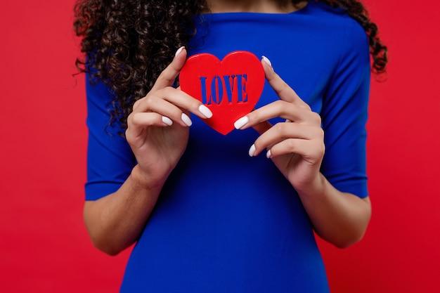 Figura em forma de coração com cartas de amor nas mãos da mulher negra na parede vermelha