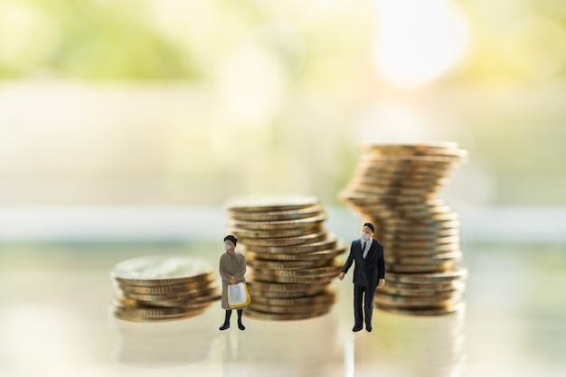 Figura em miniatura de empresário e mulher pessoas com máscara facial em pé com uma pilha instável de moedas.