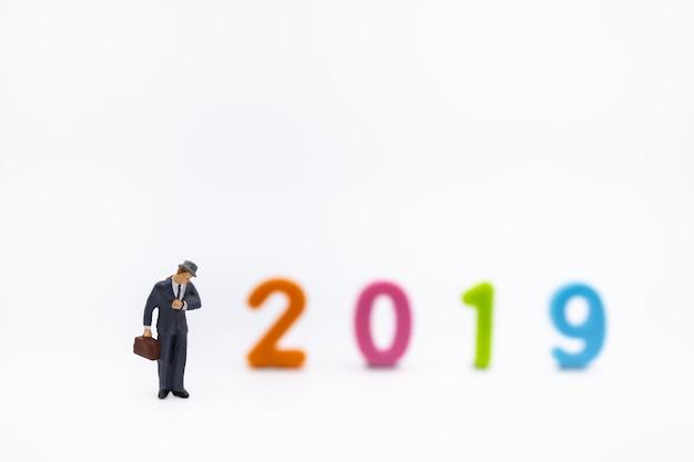 Figura em miniatura de empresário olhando para o relógio de pulso em branco com 2019 número de plástico colorido.