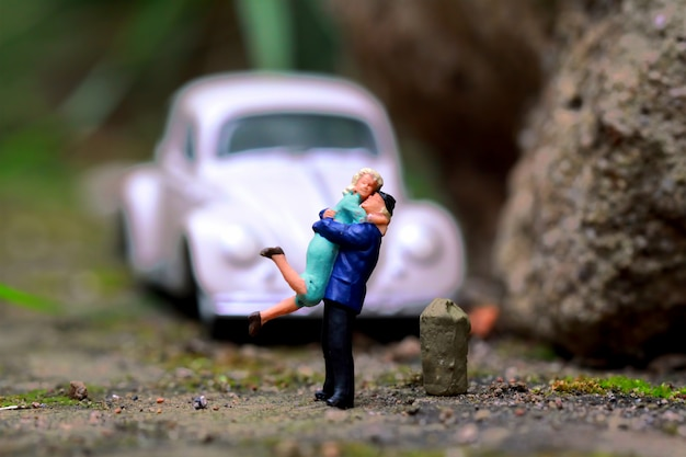 Figura em miniatura de um casal com um carro velho