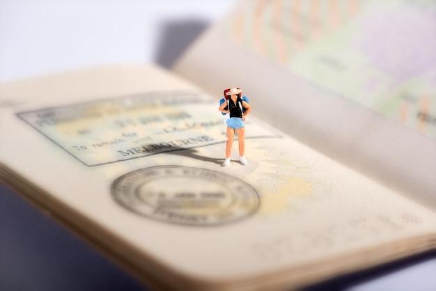 Figura em miniatura de um viajante em um passaporte