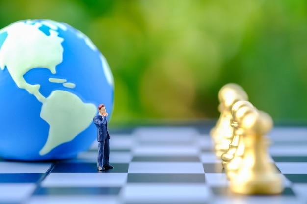 Figura em miniatura do empresário pessoas em pé no tabuleiro de xadrez com a mini bola mundial