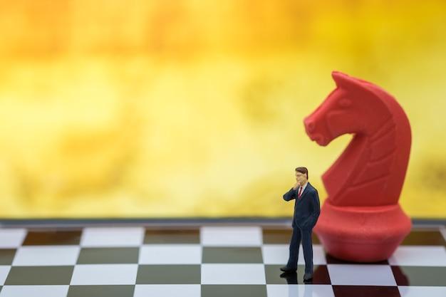 Figura em miniatura do empresário pessoas em pé no tabuleiro de xadrez com uma peça de xadrez do cavaleiro