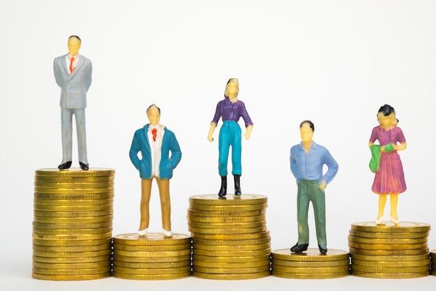 Figura empresário em miniatura em pé na pilha de moedas