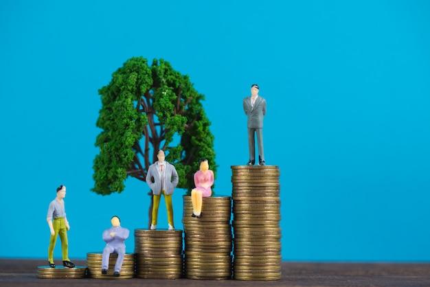 Figura empresário em miniatura na pilha de moedas com pequena árvore