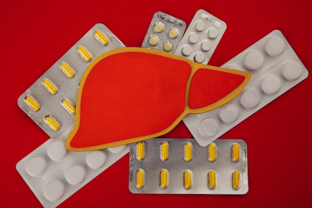 Figura fígado rodeado por pílulas sobre fundo vermelho.