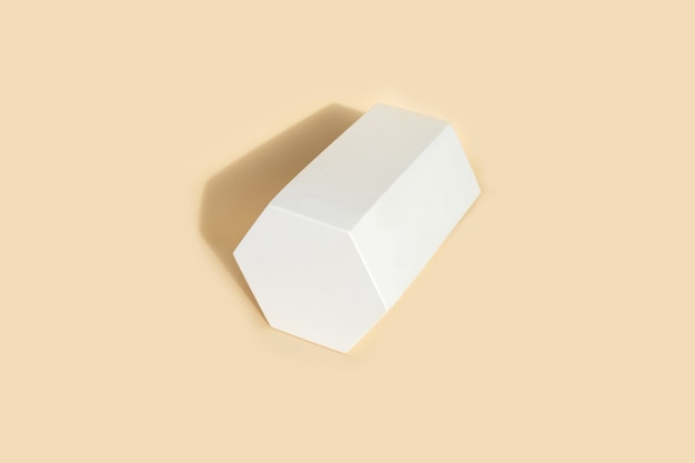 Figura geométrica prisma hexaconal na cor branca que projeta forma na cor bege pastel