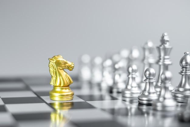 Figura gold chess knight (cavalo) no tabuleiro de xadrez contra oponente ou inimigo.
