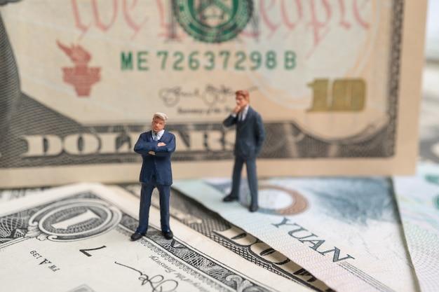 Figura homem de negócios que está no dólar americano e nota e pensamento de yuan.