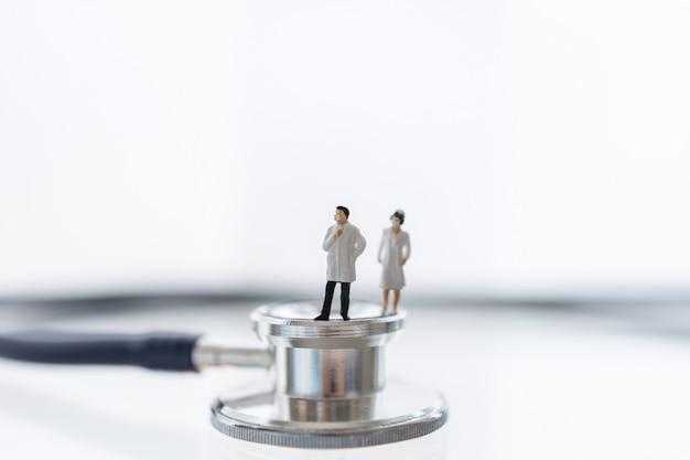 Figura miniatura de médico e enfermeiro usando máscara cirúrgica em pé no estetoscópio
