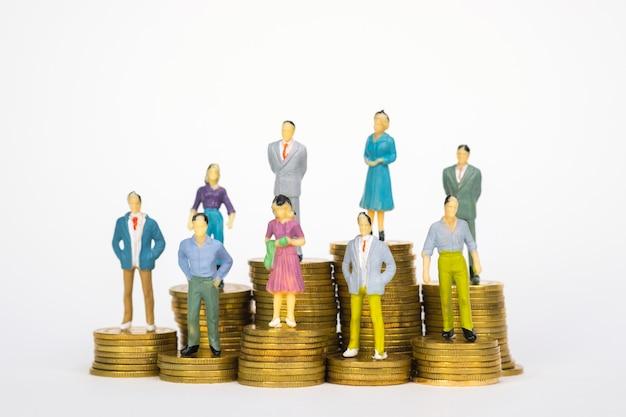 Figura miniatura empresário e trabalhador de escritório permanente na pilha de moedas