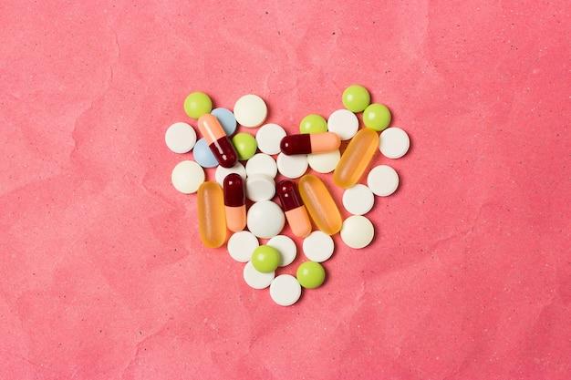 Figura na forma de um coração alinhado comprimidos e cápsulas. vista do topo.