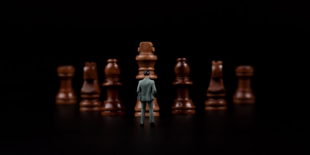 Figura o homem de negócios que está na frente da xadrez de madeira no fundo isolado preto.