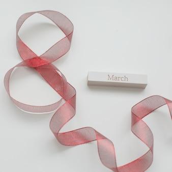 Figura oito da fita vermelha e da palavra março em fundo branco.
