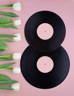 Figura oito, feita com discos de vinil vintage e tulipas brancas em fundo rosa.