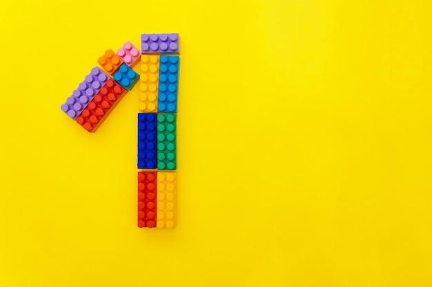 Figura um do construtor multicolorido das crianças em um fundo amarelo. espaço vazio para o texto. primeiro lugar ou 1 ano.