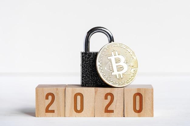 Figuras 2020 em cubos de madeira em um fundo branco ao lado de uma moeda de bitcoin
