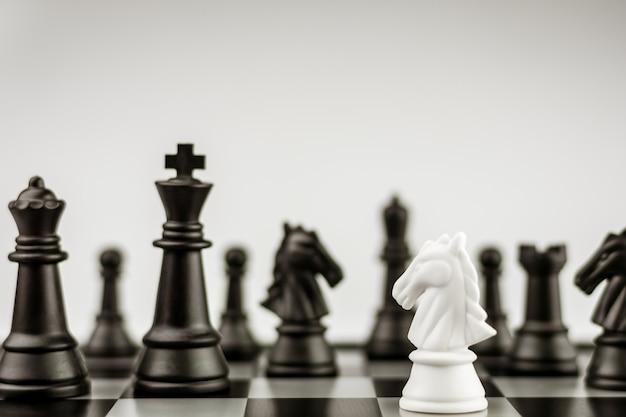 Figuras da xadrez do cavalo branco a bordo - ideia do negócio para a competição.