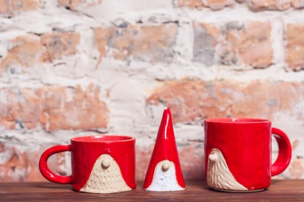 Figuras de cerâmica gnomo e duas xícaras no fundo da parede de tijolo. feito à mão.
