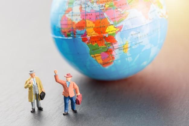 Figuras de empresários em miniatura perto de modelo de mapa mundo globo terra