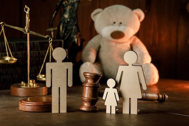Figuras de família em madeira com ursinho de pelúcia e martelo em um tribunal. conceito de divórcio e pensão alimentícia