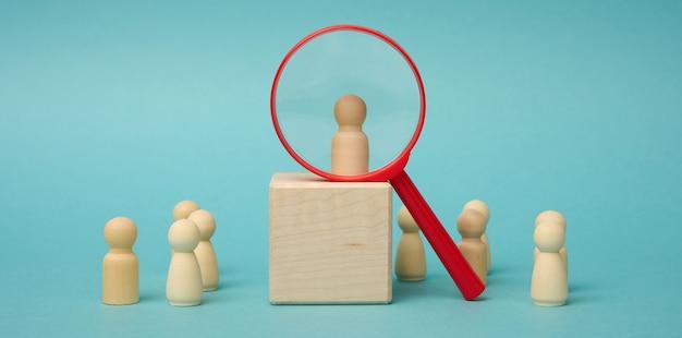 Figuras de homens em madeira estão sobre um fundo bege e uma lupa de plástico vermelha. conceito de recrutamento, busca por funcionários talentosos e capazes, crescimento na carreira