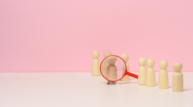 Figuras de homens em madeira ficam sobre um fundo rosa e uma lupa de plástico vermelha. conceito de recrutamento, busca por funcionários talentosos e capazes, crescimento de carreira, espaço de cópia