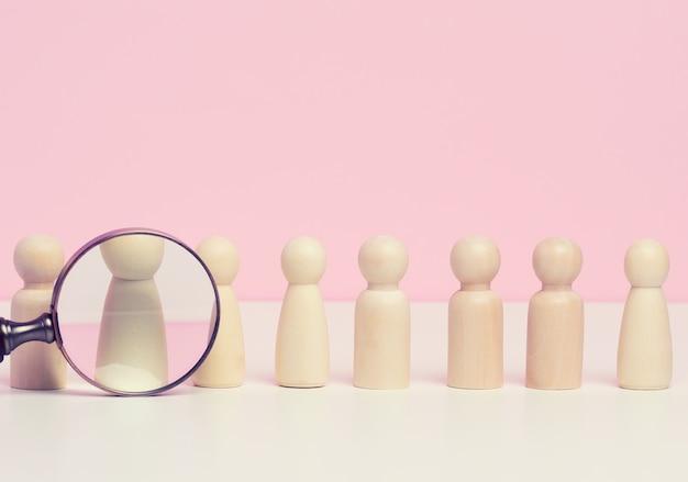 Figuras de homens em madeira ficam sobre um fundo rosa e uma lupa de plástico vermelha. conceito de recrutamento, busca por funcionários talentosos e capazes, crescimento na carreira