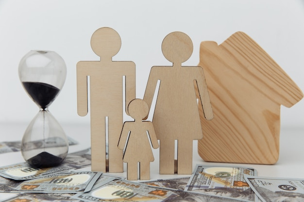 Figuras de madeira da família com conceito de economia e lucro de closeup de ampulheta e casa